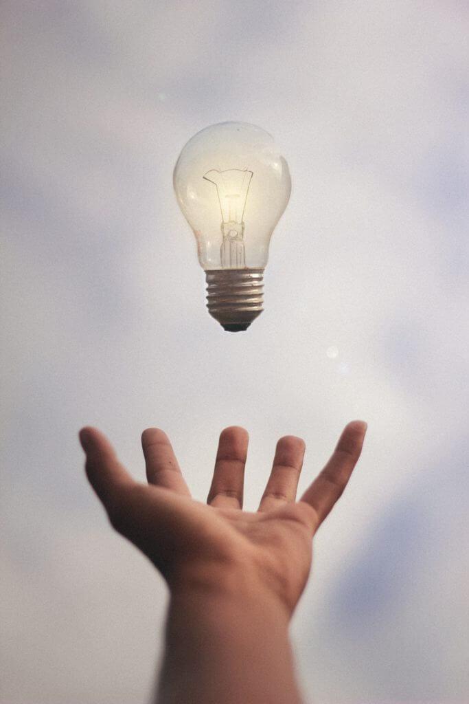 Software Entwicklung Glühbirne schwebt über Hand